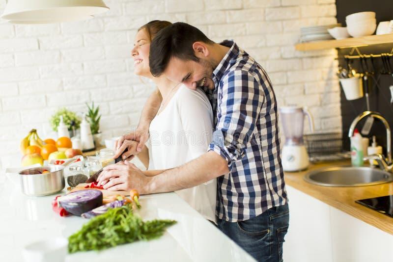 Pares cariñosos que preparan la comida sana foto de archivo