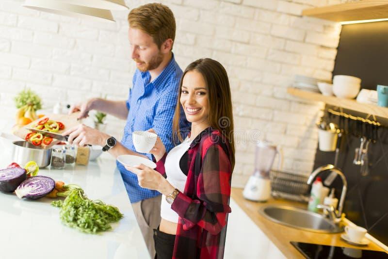 Pares cariñosos que preparan la comida sana imagen de archivo