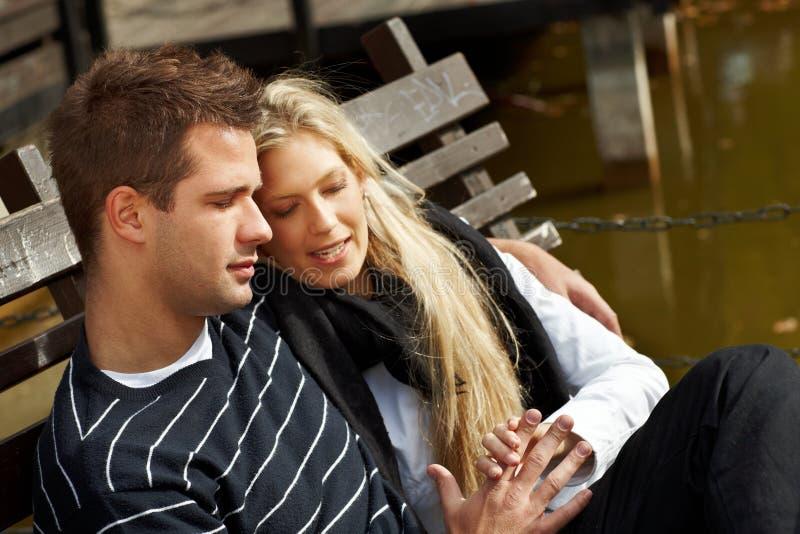 Pares cariñosos que se reclinan sobre banco en parque imagen de archivo