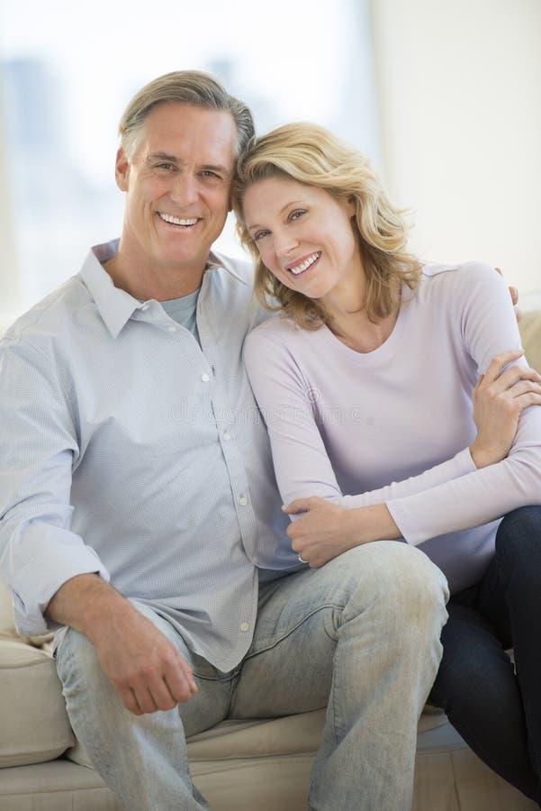 Pares cariñosos que sonríen junto en casa imagenes de archivo