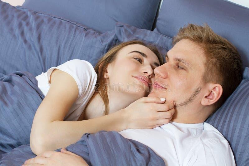 Pares cari?osos despertados hermosos en cama por la ma?ana Pares heterosexuales adultos jovenes que mienten en cama en dormitorio fotografía de archivo