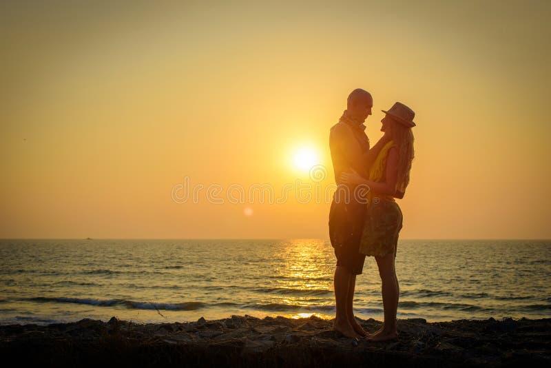 Pares cari?osos elegantes que se abrazan en la playa en la puesta del sol Hombre y mujer en viaje de la luna de miel del d?a de f imágenes de archivo libres de regalías