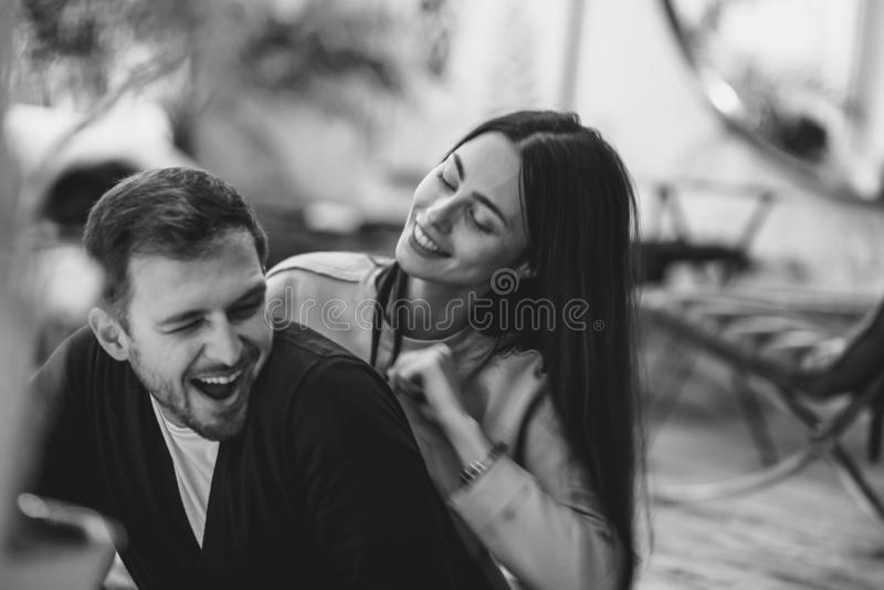 Pares cari?osos La muchacha abraza a su novio que se sienta en el café romántico acogedor Foto blanco y negro de Pek?n, China fotos de archivo libres de regalías