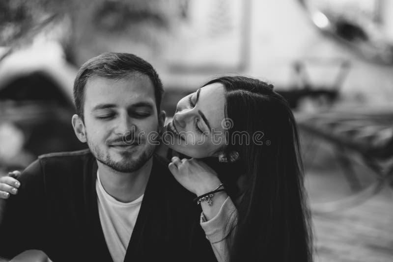 Pares cari?osos La muchacha abraza a su novio que se sienta en el café romántico acogedor Foto blanco y negro de Pek?n, China foto de archivo libre de regalías