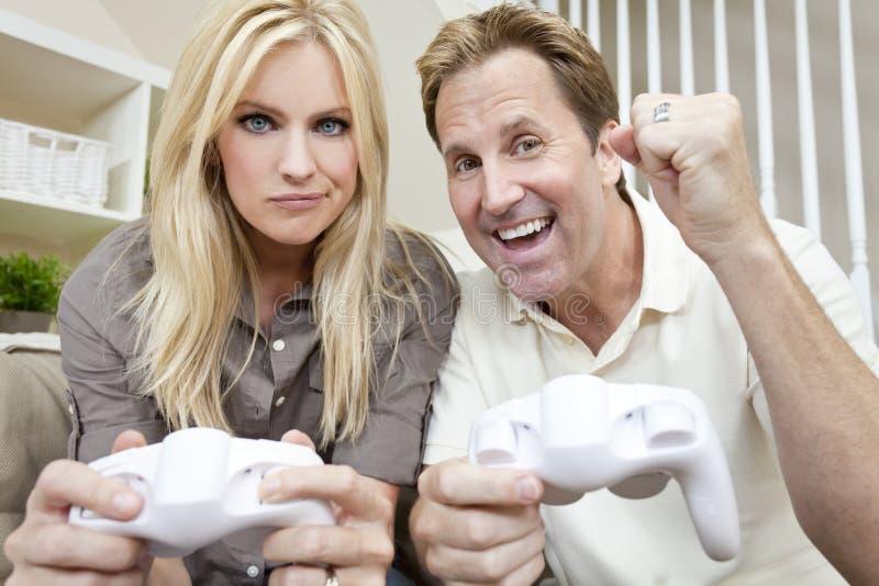 Pares casados que se divierten el jugar del juego video fotos de archivo libres de regalías