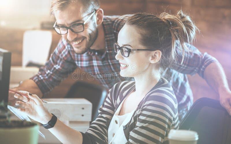 Pares casuales del negocio usando el ordenador en la oficina Dos colegas que trabajan junto en un diseño de producto innovador fotos de archivo libres de regalías
