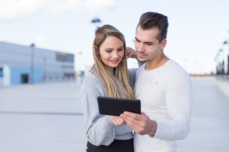 Pares casuales jovenes usando compras en línea del aire libre de la tableta fotos de archivo