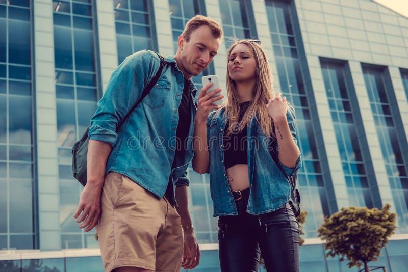 Pares casuales usando smartphone y la presentación sobre el edificio de cristal foto de archivo libre de regalías