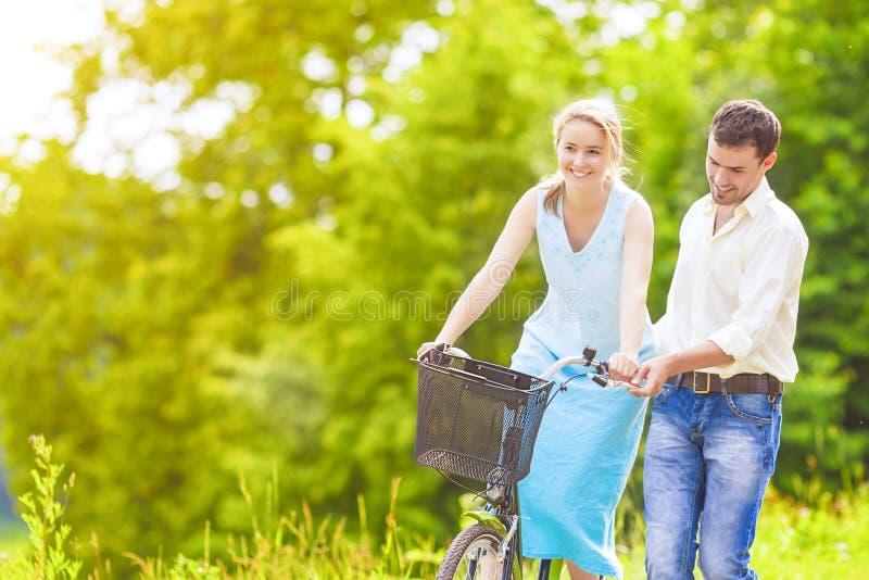 Pares caucásicos cariñosos felices que se divierten junto que monta al Ou de la bici imagen de archivo