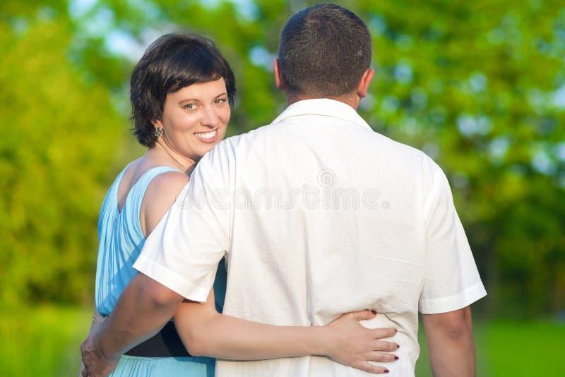 Pares caucásicos cariñosos que tienen tiempo junto abrazado al aire libre en parque del verano imagenes de archivo
