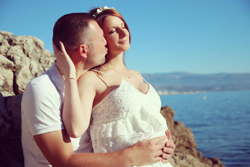 Pares caucásicos embarazadas en amor en la playa fotografía de archivo