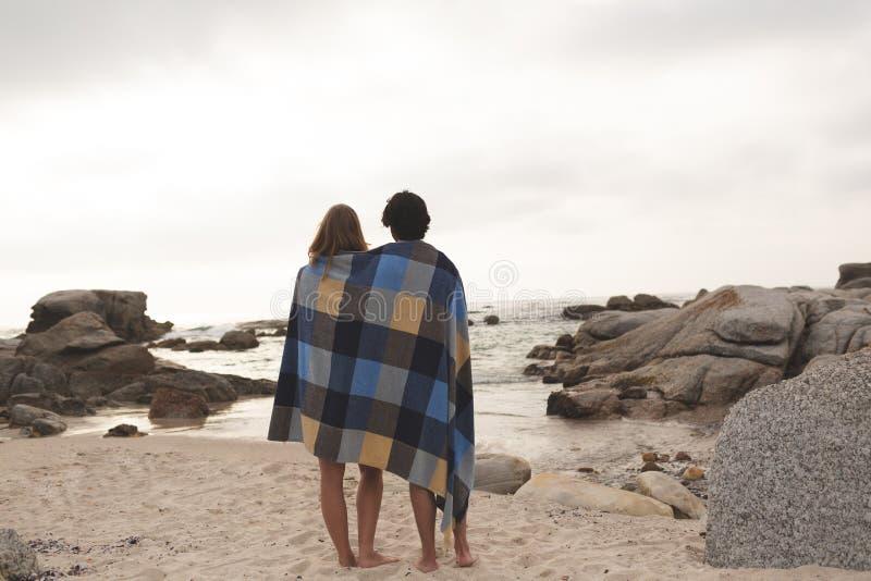 Pares caucásicos envueltos en la situación combinada en la playa foto de archivo libre de regalías