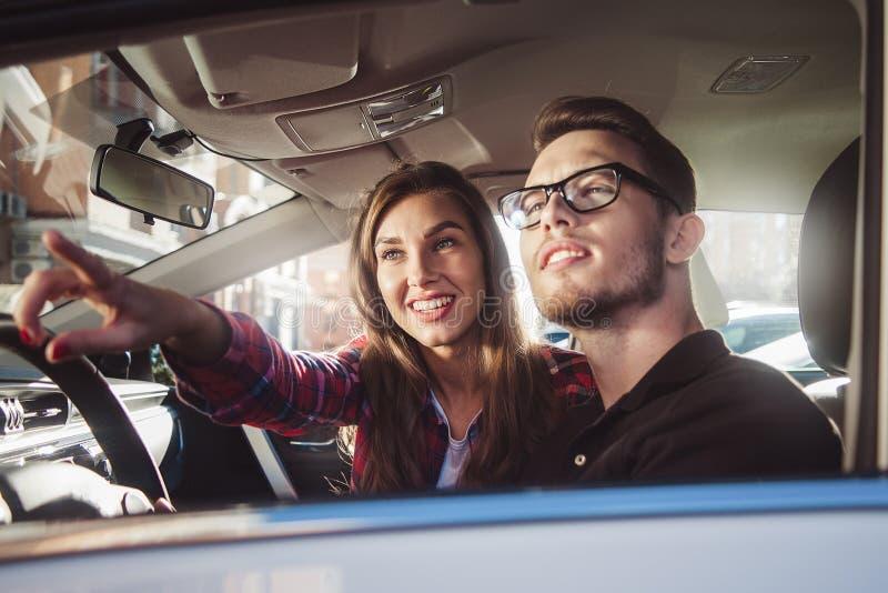 Pares caucásicos jovenes en el coche que se divierte en viaje por carretera fotografía de archivo libre de regalías