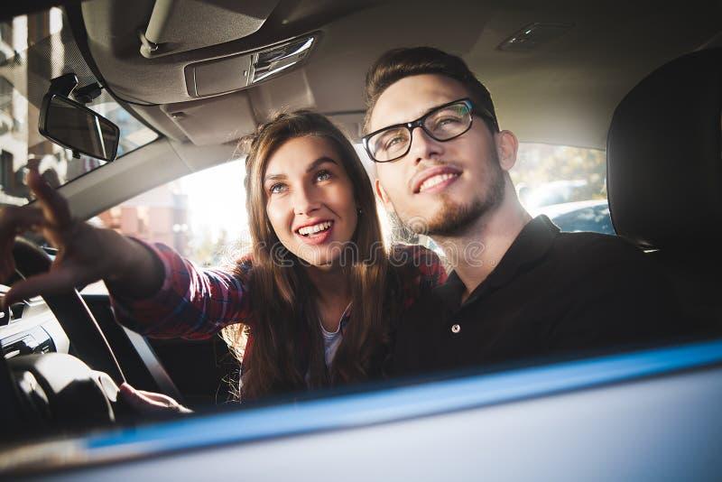 Pares caucásicos jovenes en el coche que se divierte en viaje por carretera imagen de archivo libre de regalías