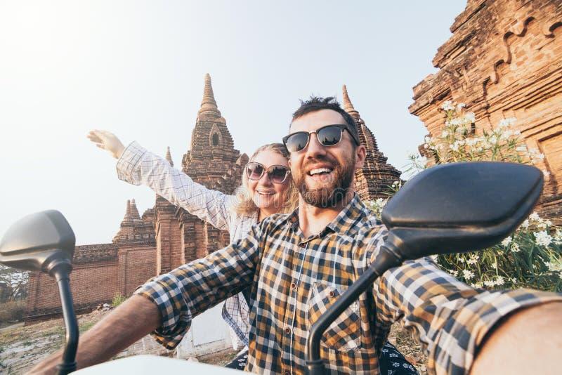 Pares caucásicos jovenes que hacen el selfie en una vespa mientras que conduce a través de los templos y de las pagodas de Bagan  imagen de archivo