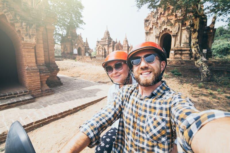 Pares caucásicos jovenes que hacen el selfie en una vespa mientras que conduce a través de los templos y de las pagodas de Bagan  foto de archivo libre de regalías
