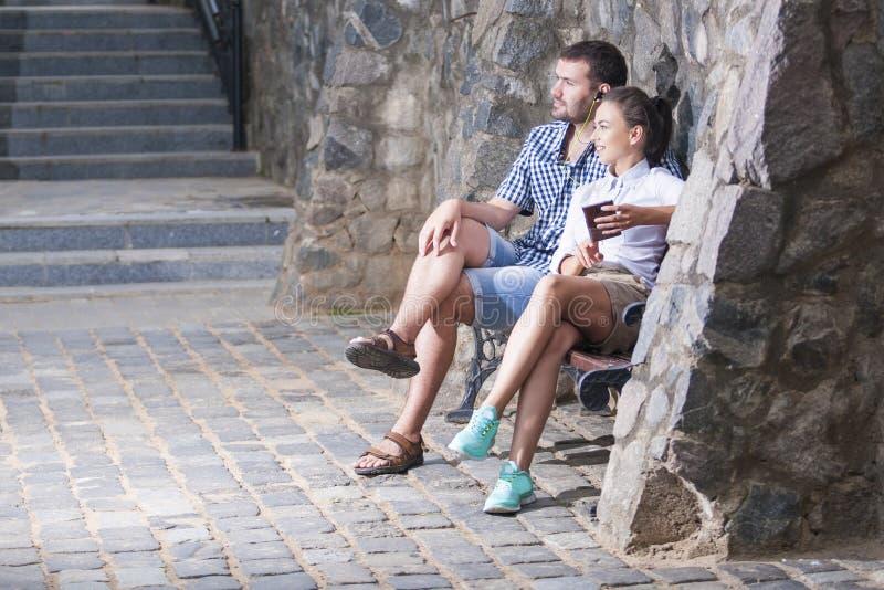 Pares caucásicos positivos relajantes que se sientan junto abrazado al aire libre foto de archivo libre de regalías