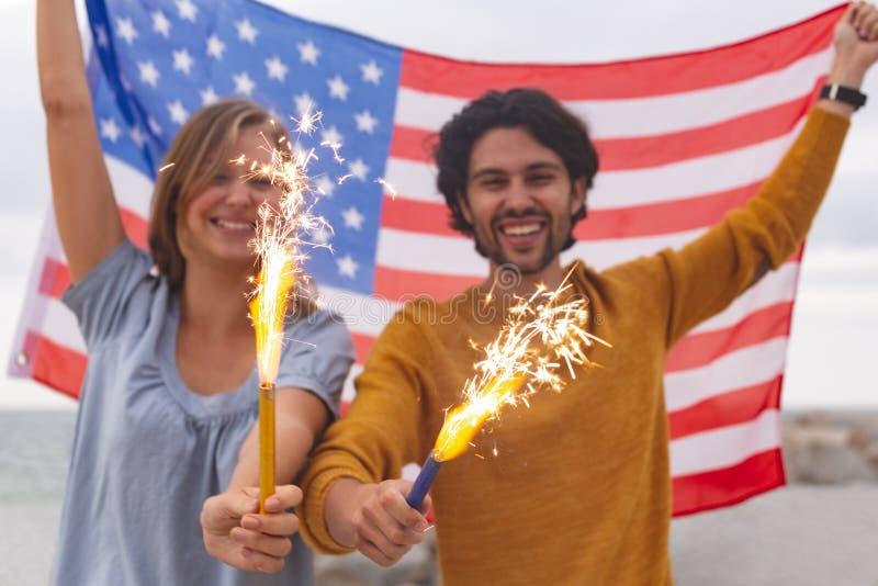 Pares caucásicos que juegan con la galleta del fuego mientras que sostiene la bandera americana imagen de archivo