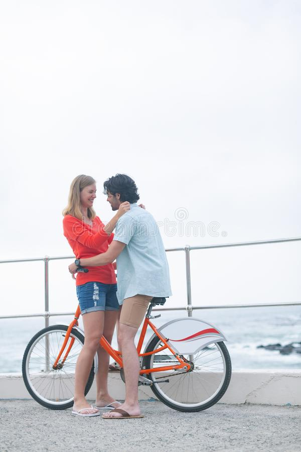 Pares caucásicos románticos embarazosos en ciclo en la playa imágenes de archivo libres de regalías