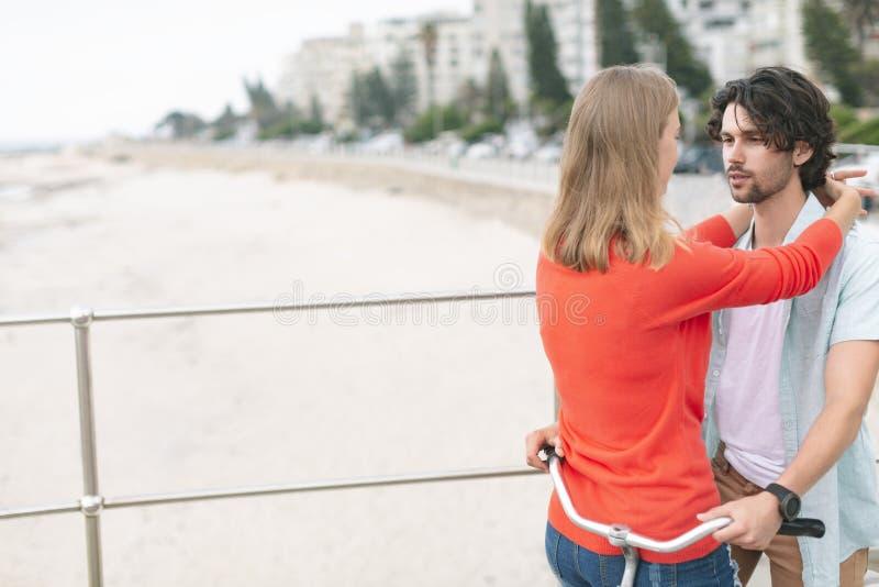 Pares caucásicos románticos embarazosos en ciclo en la playa foto de archivo