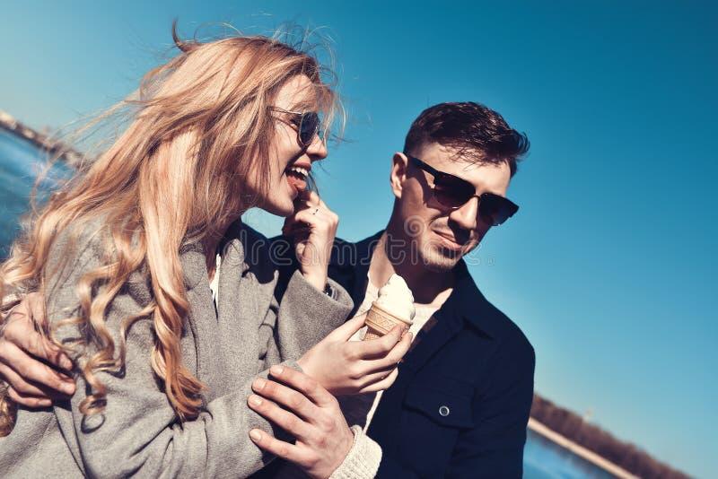 Pares caucásicos románticos felices en gafas de sol La muchacha divertida come el helado foto de archivo libre de regalías