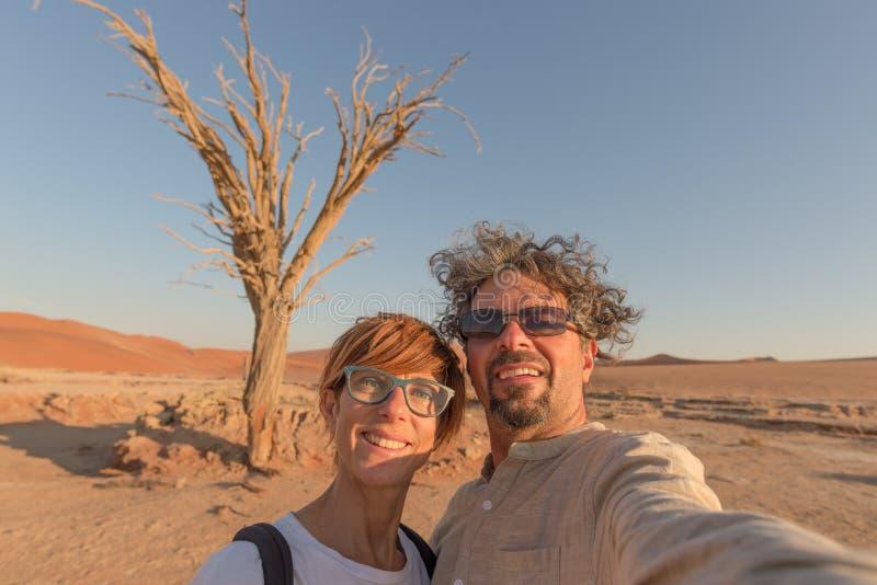 Pares caucasianos adultos que tomam o selfie em Sossusvlei no deserto de Namib, parque nacional de Namib Naukluft, destino princi imagem de stock royalty free