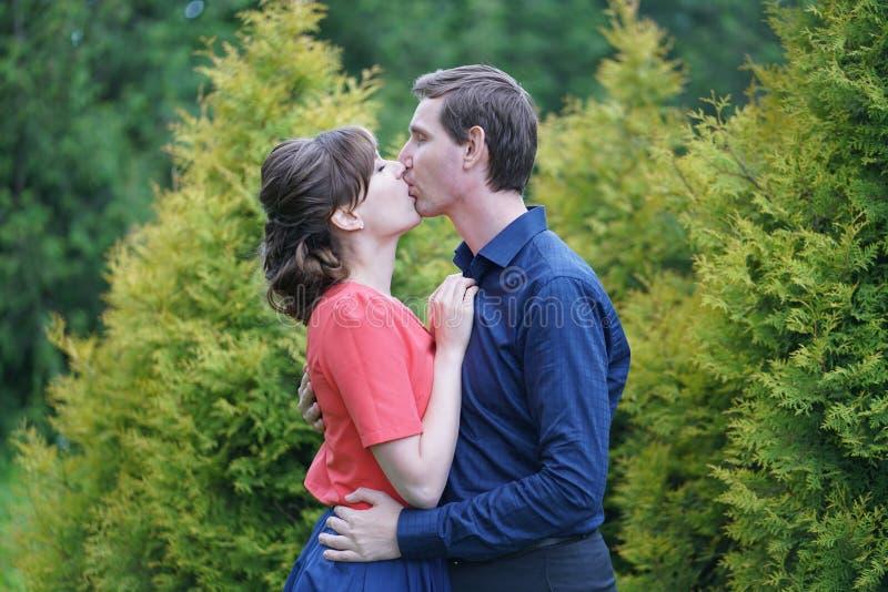 Pares caucasianos bonitos do amor que andam no parque verde do verão, tendo sorrisos, beijos e abraços foto de stock