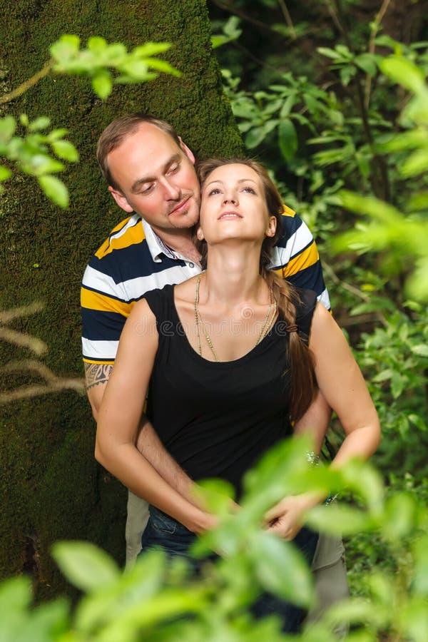 Pares caucasianos de amor felizes novos que abraçam e que sonham exteriores no conceito romântico do relacionamento da floresta d foto de stock