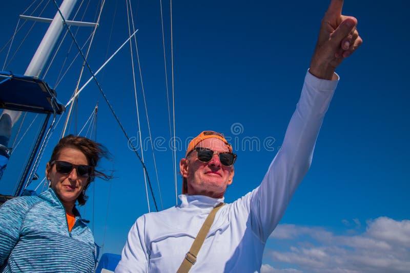 Pares caucasianos do nascido no Baby Boom mais idoso com o homem que aponta na distância Céu azul profundo com equipamento do vel fotografia de stock