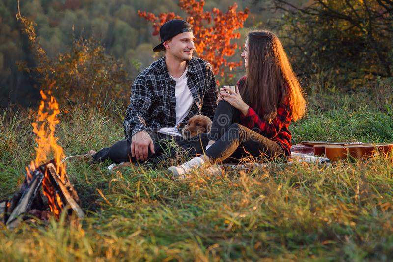 Pares caucasianos felizes com seu cão engraçado que senta-se no gramado no parque da mola Homem novo e sua amiga que apreciam em fotografia de stock