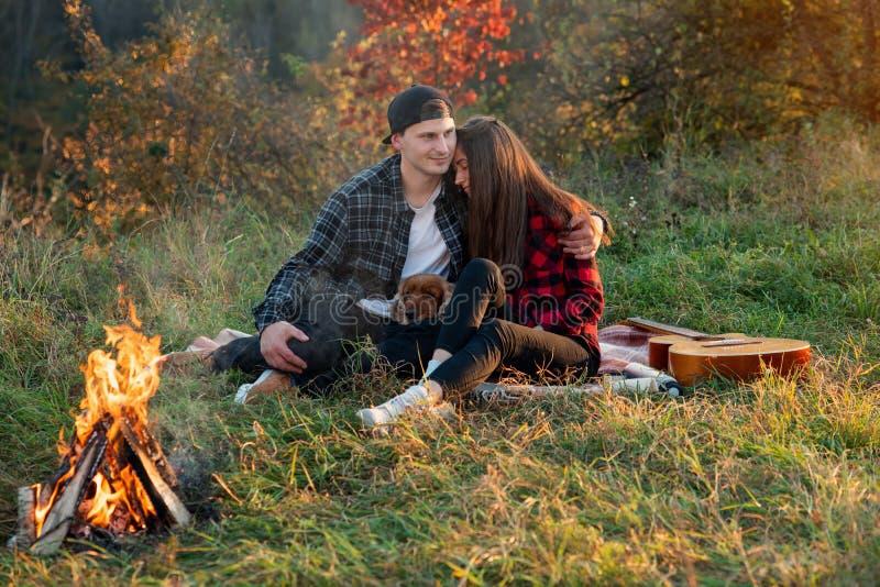 Pares caucasianos felizes com seu cão engraçado que senta-se no gramado no parque da mola A menina bonita nova inclinou-se contra fotos de stock royalty free