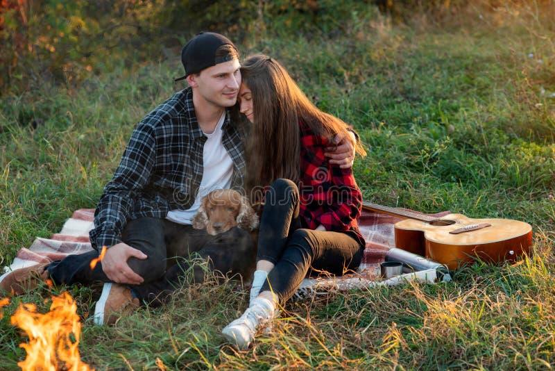 Pares caucasianos felizes com seu cão engraçado que senta-se no gramado no parque da mola A menina bonita nova inclinou-se contra fotografia de stock royalty free
