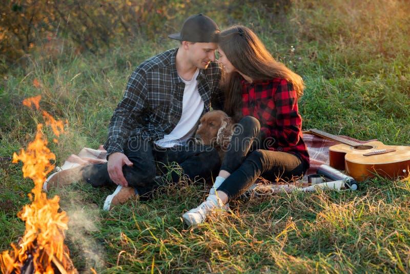Pares caucasianos felizes na roupa ocasional com seu cão engraçado que senta-se no gramado no parque da mola Menina bonita nova fotografia de stock royalty free