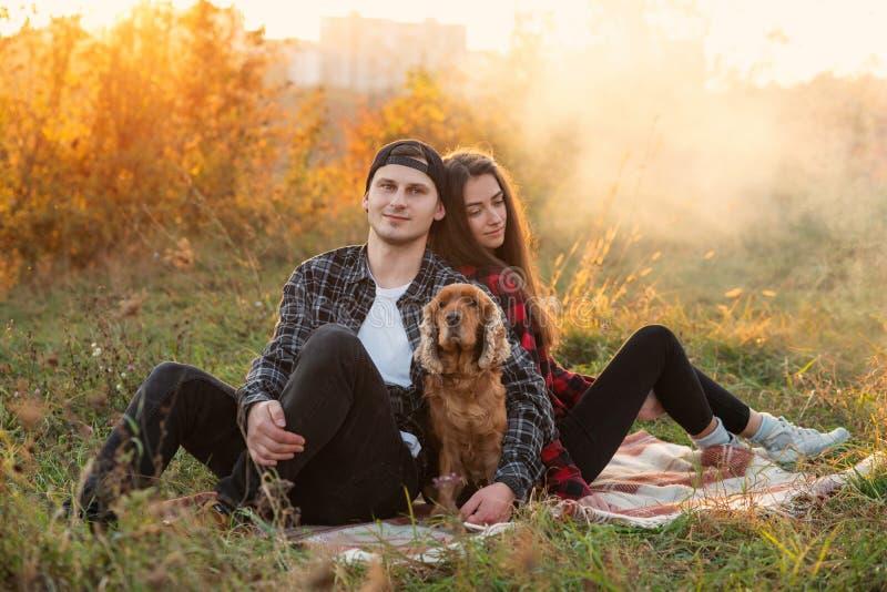 Pares caucasianos felizes na roupa ocasional com seu cão que tem o resto no gramado no parque da mola Menina bonita nova fotografia de stock royalty free