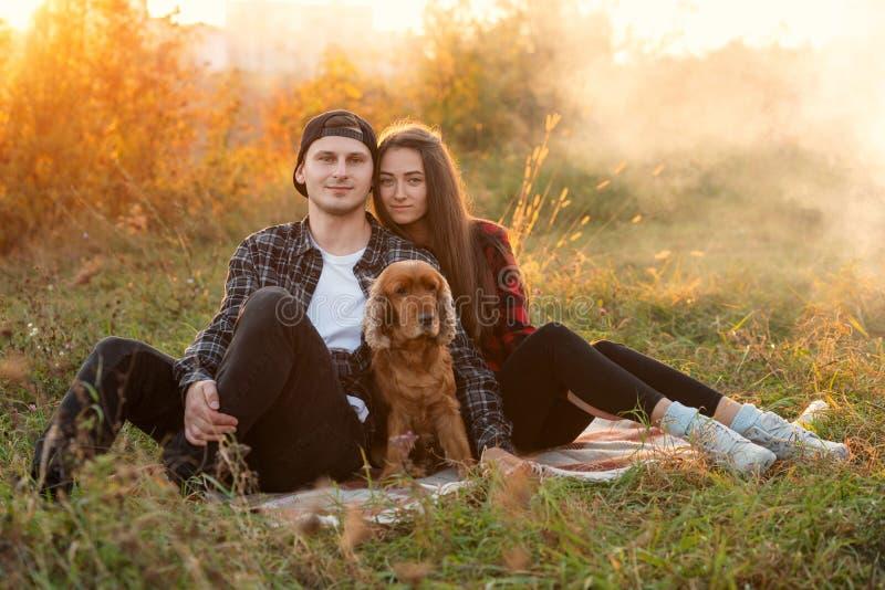 Pares caucasianos felizes na roupa ocasional com seu cão que tem o resto no gramado no parque da mola Menina bonita nova foto de stock royalty free