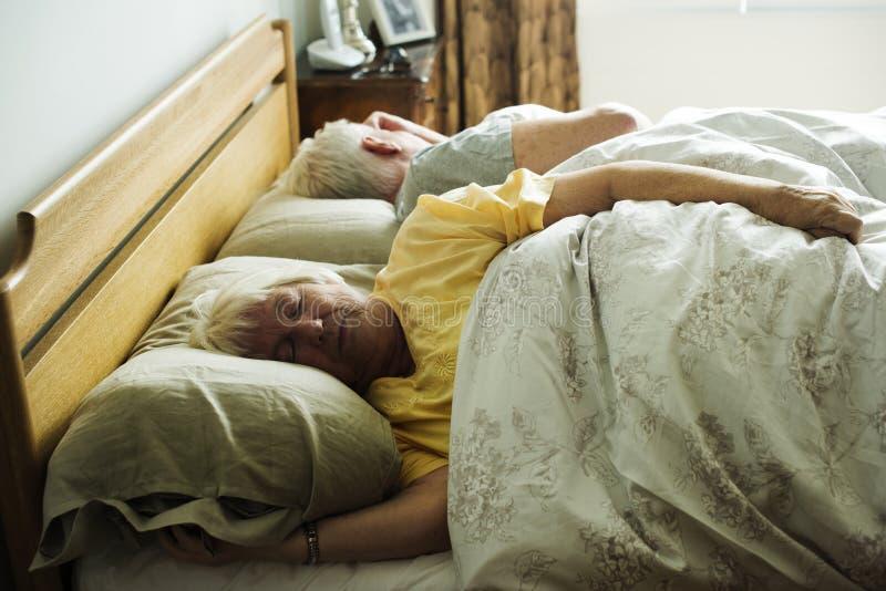 Pares caucasianos idosos que dormem na cama imagens de stock