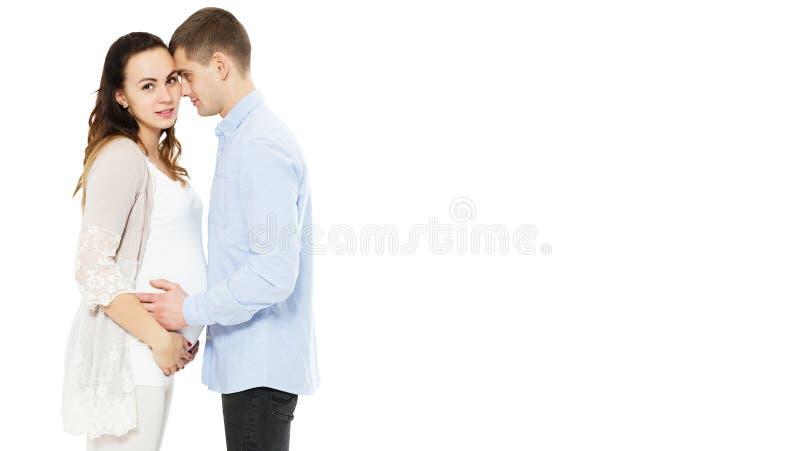 Pares caucasianos novos: mãe grávida e pai feliz no fundo branco, bebê carregado imagem de stock