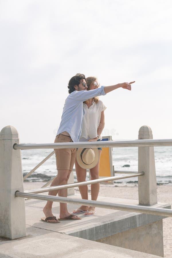 Pares caucasianos que interagem um com o otro no passeio no beira-mar foto de stock