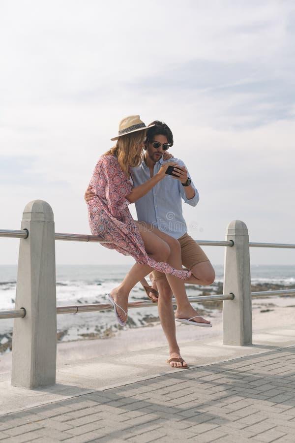 Pares caucasianos que revivem fotos ao sentar-se em trilhos na praia imagens de stock