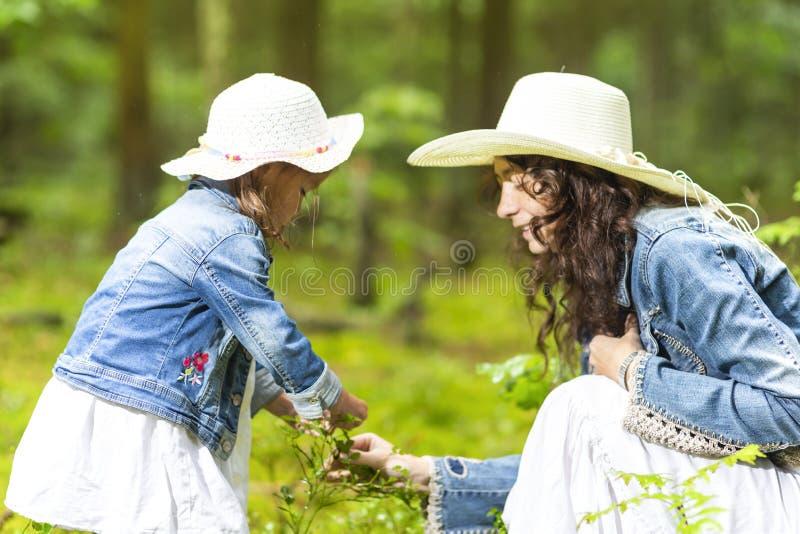 Pares caucasianos tranquilos e positivos de mãe e de filha pequena que têm o tempo junto na floresta verde do verão imagens de stock