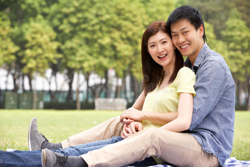 Pares chineses novos que relaxam no parque junto foto de stock
