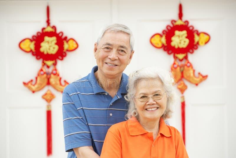 Pares chineses sênior fora da HOME com Feng Shui fotos de stock