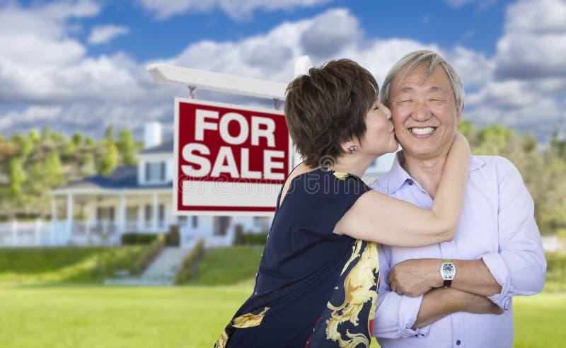 Pares chineses superiores afetuosos na frente da casa e do sinal fotos de stock royalty free