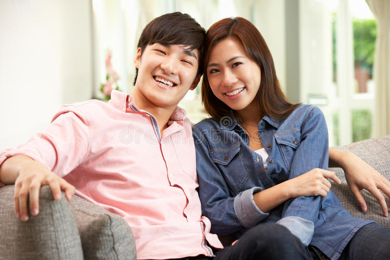 Pares chinos jovenes que se relajan en el sofá en el país imagen de archivo libre de regalías