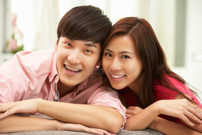 Pares chinos jovenes que se relajan en el sofá en el país foto de archivo libre de regalías