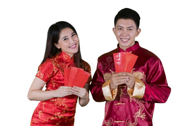 Pares chinos jovenes que sostienen sobres en estudio fotos de archivo libres de regalías