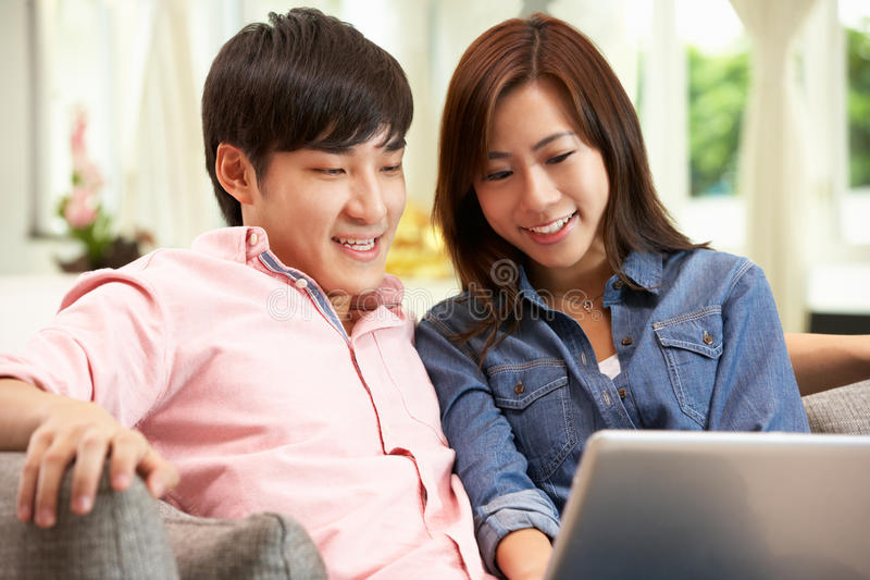 Pares chinos jovenes usando la computadora portátil mientras que se relaja fotografía de archivo