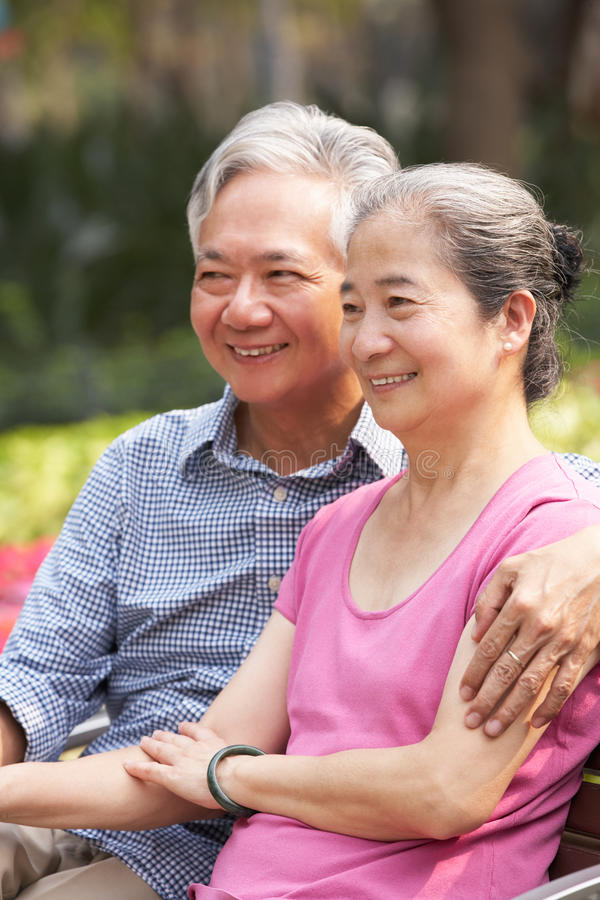 Pares chinos mayores que se relajan en banco de parque fotografía de archivo libre de regalías