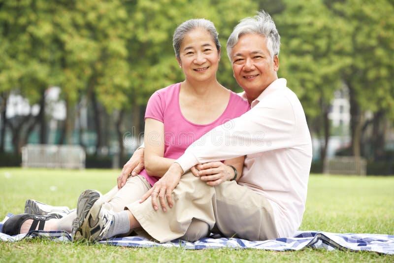 Pares chinos mayores que se relajan en parque junto imagenes de archivo
