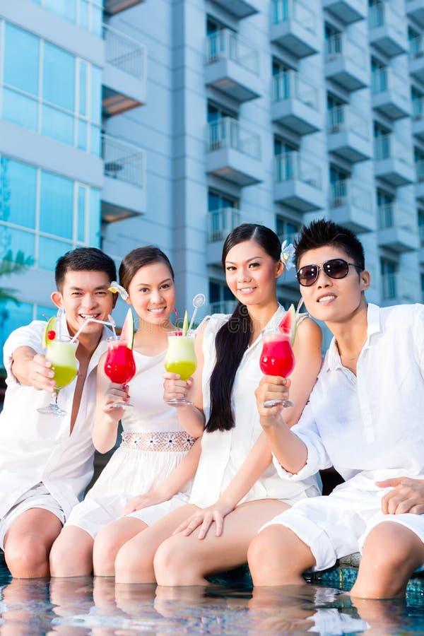 Pares chinos que beben los cócteles en barra de la piscina del hotel imagen de archivo libre de regalías